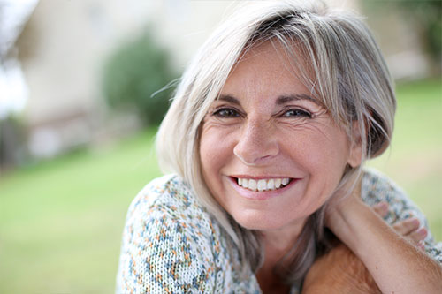 Older woman with grey hair smiling at the camera with a blurred out park scene in the background