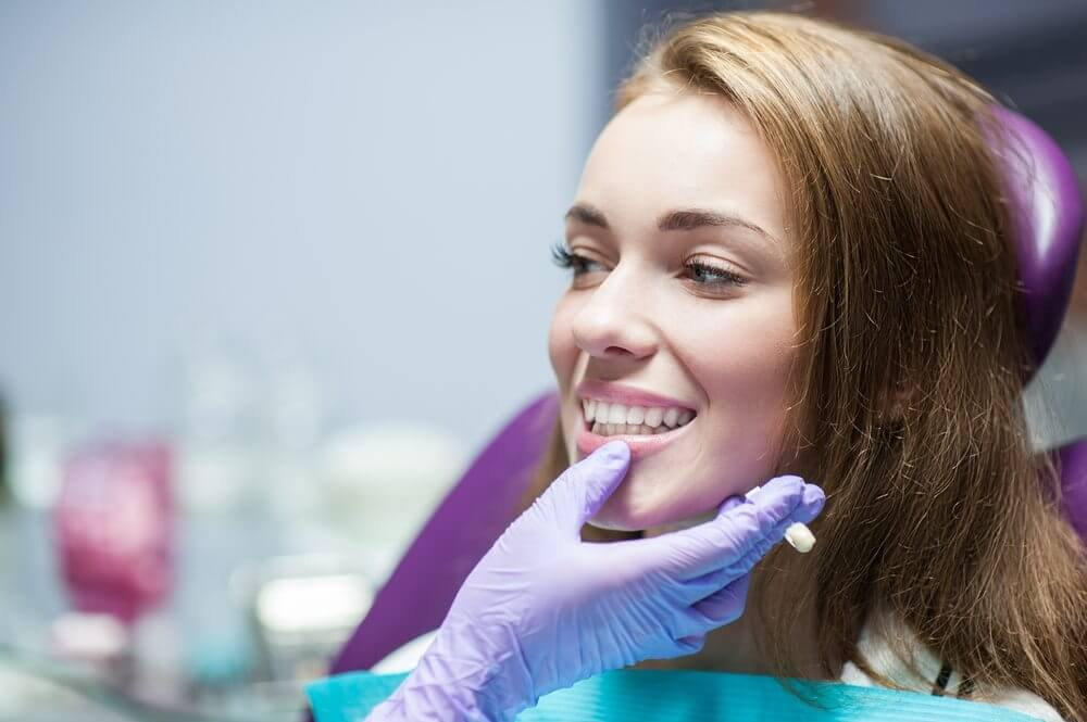 A female sitting in a purple dental chair while looking at the dentist