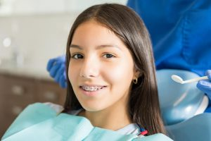 A close-up of a young girl smiling with braces while sitting in the dental chair