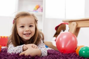 Little girl laying on her stomach and smiling by balloons
