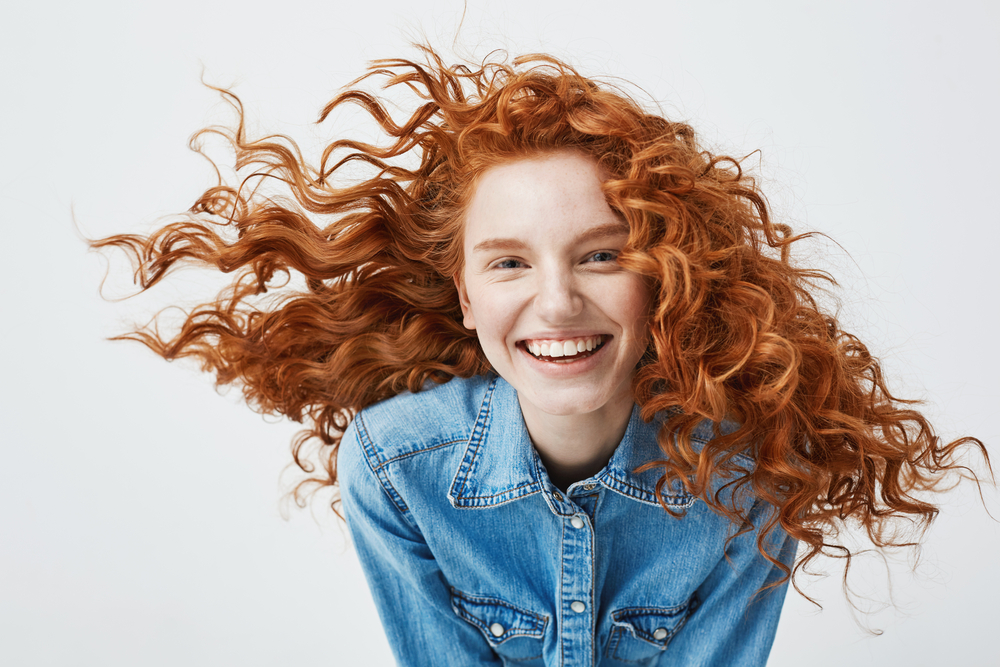 young red-haired woman smiles in front of a white background