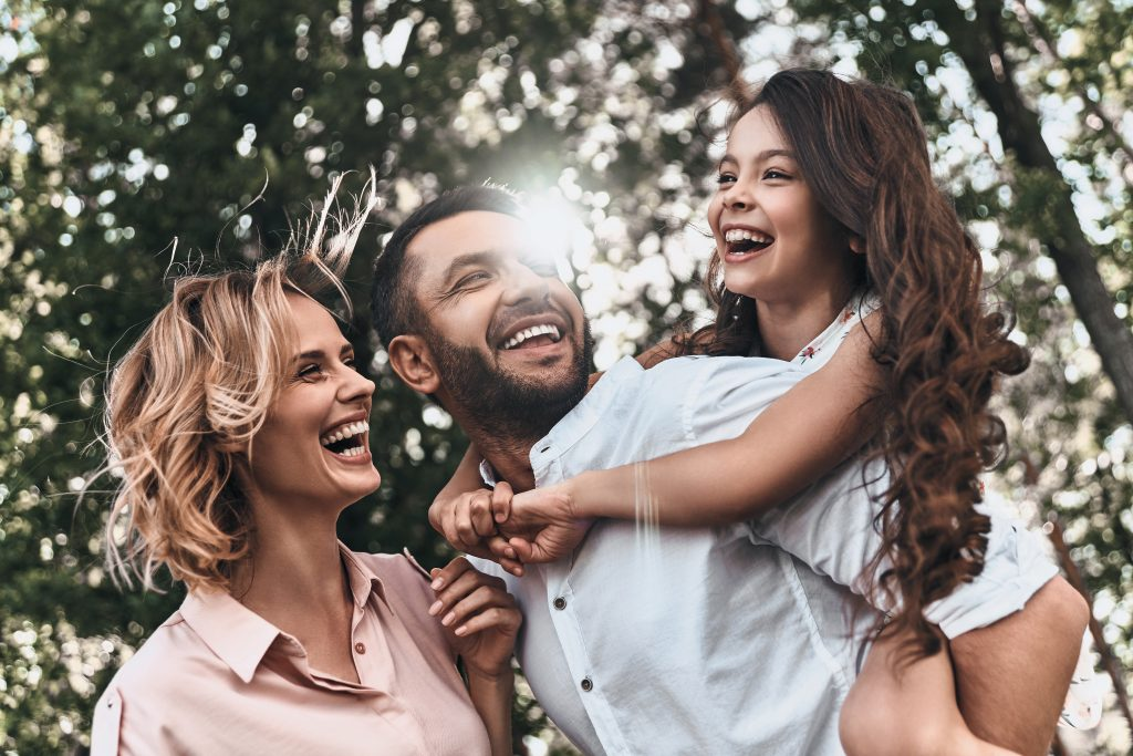 Family smiling under tree
